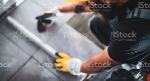 A young bearded man in overalls using a level to check the alignment of the tiles he is laying.